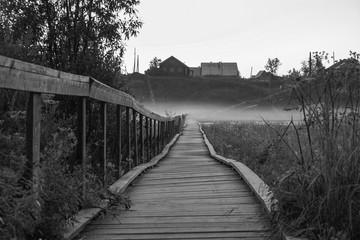 Old wooden bridge to village hill. Vintage gothic rustic black and white photo