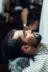 portrait of handsome man with beard in barbershop