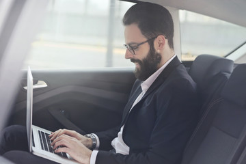 Businessman checking e-mails in the car