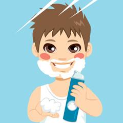 Cute little boy playing with shaving cream spray applying foam on face as fake beard