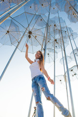 Girl holding an umbrella. Installation Flying umbrellas, Greece. Group of umbrellas on blue sky background. Concept of summer travel. Umbrellas in Thessaloniki, Greece.