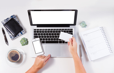 On-line shopping concept mock up - desktop with laptop and hands holging credit card, copy space on empty screen of phone, notebook and plastic card