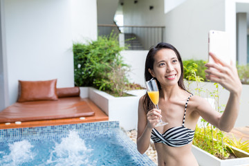 Woman drinking in spa and taking selfie