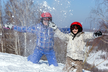 Mom and daughter, in ski equipment play with snow