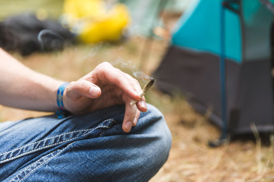 Person Holding Rolled Joint in Camping Area
