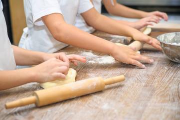 Young children make dough. Hands close up