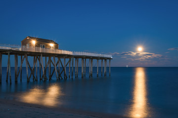 Full moon rising at Belmar Fishing Pier in New Jersey