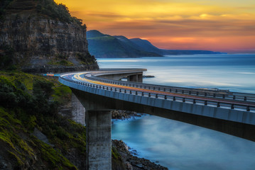Poster de jardin Océanie Sunset over the Sea cliff bridge along Australian Pacific ocean coast with lights of passing cars