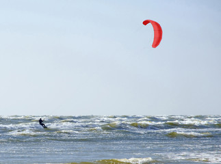Jürmala (Latvia). Surfing at the sea  with a red parachute at strong wind and waves.