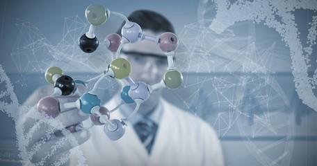 Composite image of scientist holding molecule structure