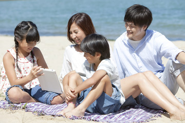 Family of four looking at digital tablet on the beach