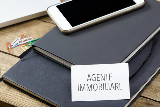 Agente immobiliare, Italian text for Realtor business card on office desktop with electronic devices