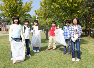 Portrait of school children holding bags for recycling