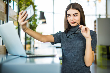 Young female taking a selfie in the office in glasses while sitting with laptop.