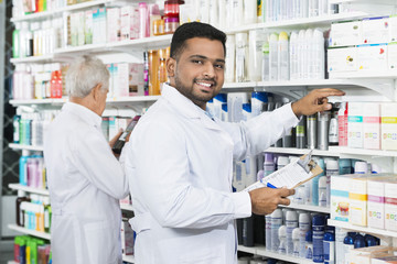 Smiling Chemist Counting Stock With Colleague In Pharmacy