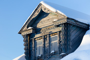 the Carved Window of an old country house in the snow against a blue sky background