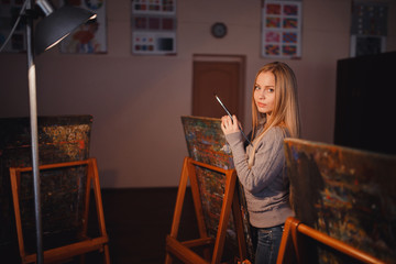 Artist beautiful girl paints a picture on canvas with watercolor in her workshop and art school. Portrait. close-up