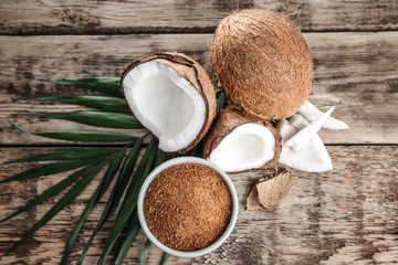 Bowl of brown sugar and coconut on wooden background