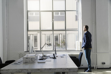Young businessman looking out of office window