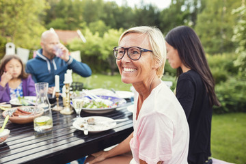 Happy woman sitting with friends and family at dining table in back yard during garden party
