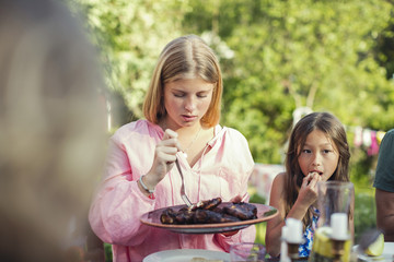 Girls eating lunch in back yard during garden party