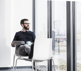 Young businessman sitting on chair using digital tablet