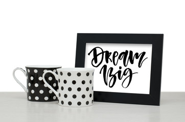 Dream big. Handwritten text, inspirational quote. Modern calligraphy. Black wooden frame. Black and white coffee Cup on the table