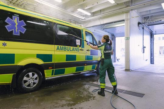 Full length rear view of female paramedic washing ambulance at parking lot