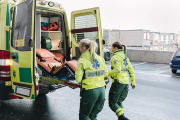 Rear view of female paramedics pushing stretcher in ambulance on street