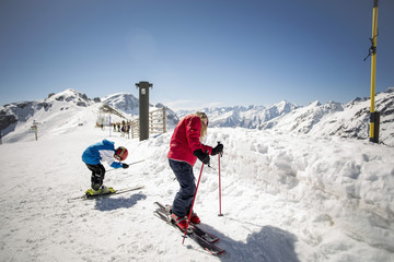Full length of brother and sister skiing against clear sky
