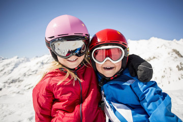 Cheerful siblings in ski-wear standing against snowcapped mountain