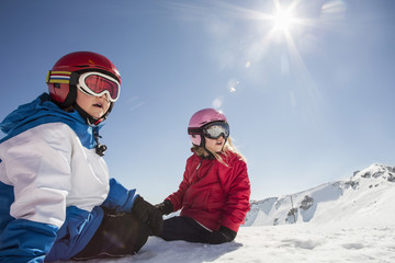 Surprised siblings sitting on snowcapped mountain against clear sky