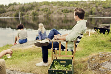 Men having drink while looking at female friends fishing on lakeshore