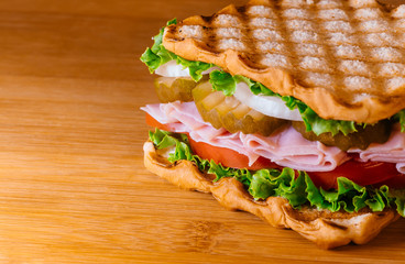 Sandwich with ham, cheese fresh vegetables on wooden cutting board