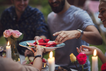 Cropped image of woman serving watermelon slices to friends at garden party