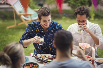 Happy men having drink while sitting with friends at table in garden party
