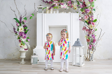 Two charming little girls play in the light room decorated with flowers.