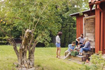 Friends spending time together outside cottage