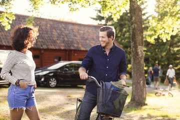 Man talking with female friend while riding bicycle at backyard