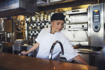Young female chef working in kitchen at restaurant