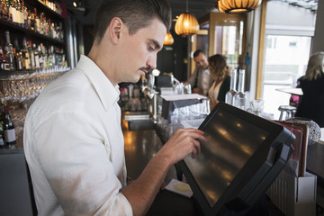 Side view of male owner using cash register at checkout in restaurant