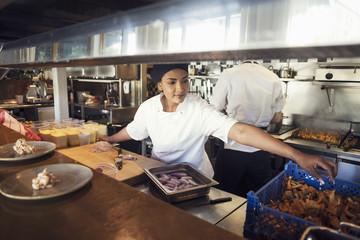 Female chef preparing food in kitchen at restaurant