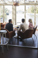 Business colleagues sitting with laptop during meeting at restaurant