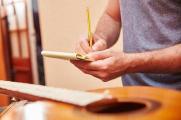 Gitarrenbauer prüft Gitarre mit Checkliste