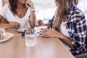Two young and beautiful women meet at the bar for a cappuccino and to chat
