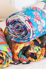 Three colored patchwork quilts twisted into close up. Colorful scrappy blankets folded as background. Handmade. DOF.