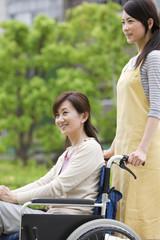 Caretaker pushing mature woman on wheelchair