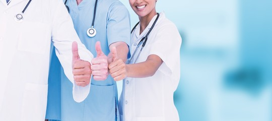 Composite image of portrait of smiling doctors with thumbs up