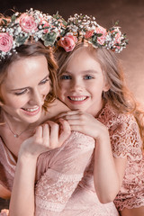 portrait of cheerful hugging daughter and mother in flowers wreathes