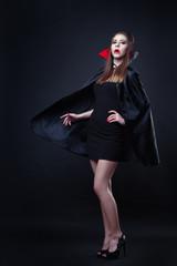 A beautiful vampire girl in a growing cloak of dracula in full growth.